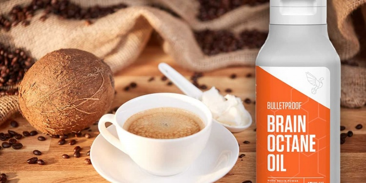 bulletproof coffee with coconut butter on white spoon on brown table next to bulletproof octane oil bottle