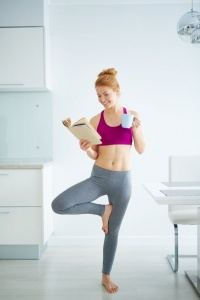 Young active woman with cup of tea reading book and doing yoga exercise in the kitchen