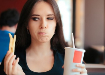 girl tempted to eat fries and drink a cup of soda