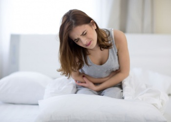 woman holding her stomach in pain