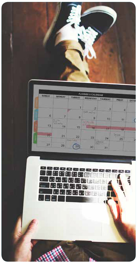 Person seated in the floor looking at the computer calendar
