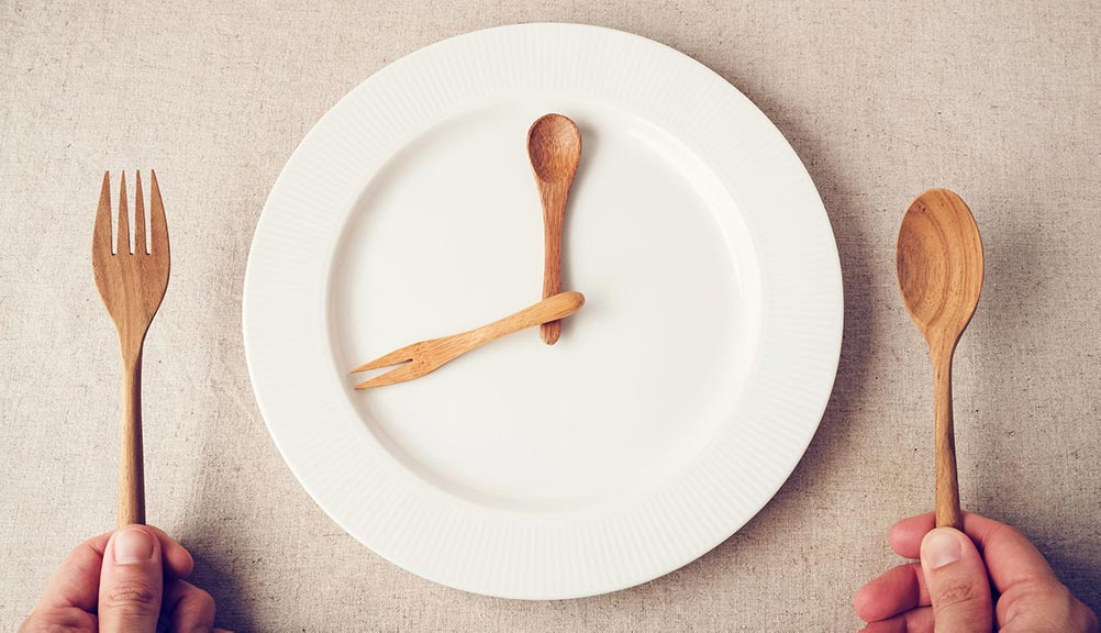 plate that looks like a clock and a person holding a fork an a spoon