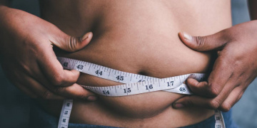 person with tape measure around their stomach
