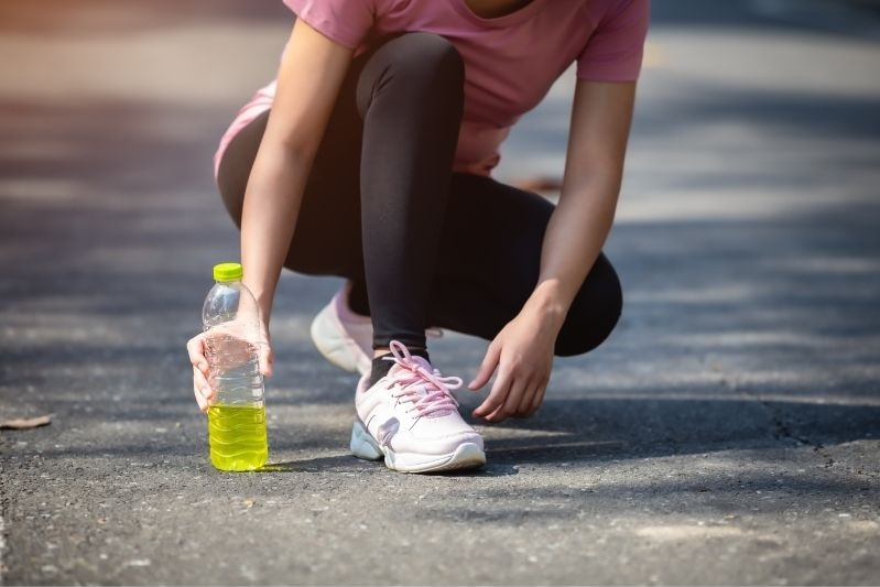 woman runner with bottle of electrolytes